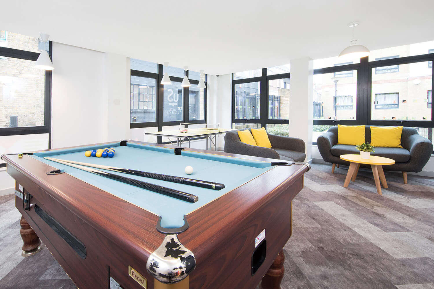 Student accommodation London pool table and sofas in common room at Pacific Court